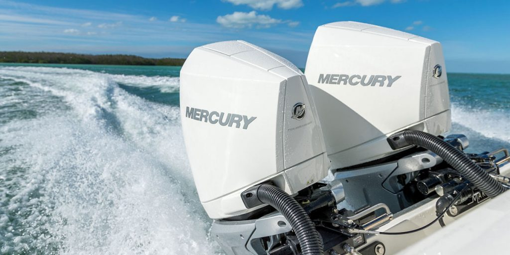 Two Mercury Engines on the back of a boat moving at speed in the water.